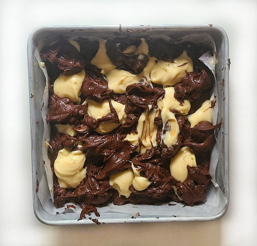 cheesecake brownie batter in the pan